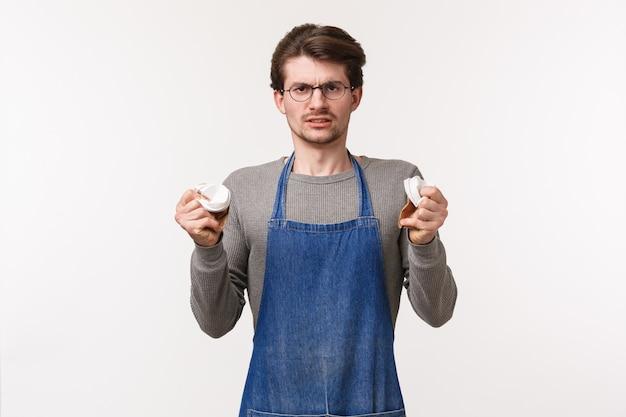 Retrato de jovem revoltado e irritado de avental, barista odeia seu trabalho, apertando copos de comida indignados e irritados, fazendo uma careta incomodada, mal-humorada