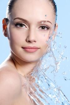 Retrato de jovem rosto feminino com respingos de água - fundo azul