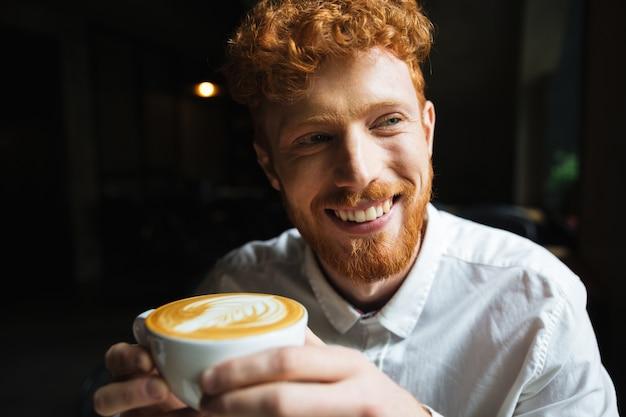 Retrato de jovem ruiva barbudo homem com sorriso encantador na camisa branca, segurando a xícara de café, olhando de lado
