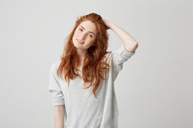 Retrato de jovem ruiva bonita com sardas sorrindo tocando o cabelo.
