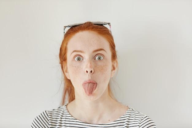 Retrato de jovem ruiva engraçada branca com sardas se divertindo dentro de casa, mostrando a língua. close-up de uma adolescente vestindo uma camisa de marinheiro da moda fazendo caretas para uma parede branca