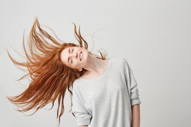Retrato de jovem ruiva linda alegre sorrindo com os olhos fechados, sacudindo a cabeça e cabelos.