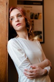 Retrato de jovem ruivo bonito branco cabelo cacheado olhando pela janela