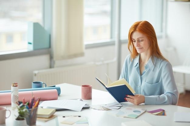 Retrato de jovem sardento lendo diário enquanto está sentado no local de trabalho criativo perto da janela, copie o espaço