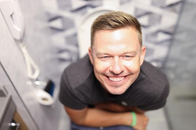 Retrato de jovem satisfeito sentado no banheiro causa diarreia no conceito adulto