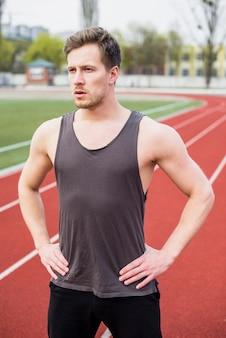 Retrato de jovem saudável com mão no quadril em pé na pista de campo
