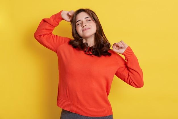 Retrato de jovem se espreguiçando e bocejando contra a parede amarela, mantém os olhos fechados, sente sono, vestindo um suéter laranja, sendo preguiçoso, acaba de acordar.