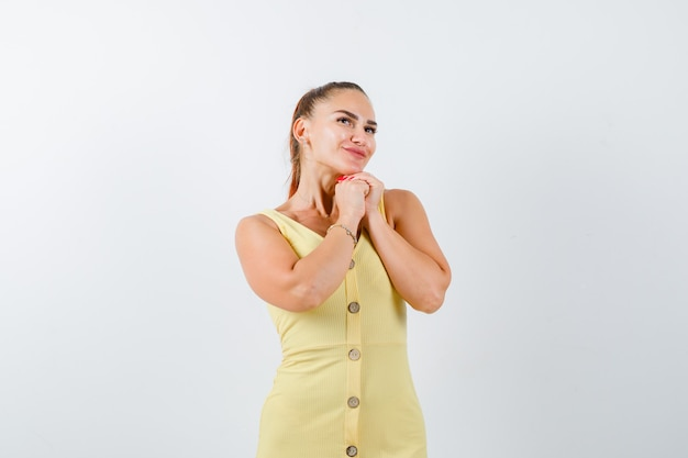 Retrato de jovem segurando as mãos em um gesto de oração, olhando para cima em um vestido amarelo
