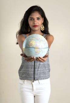 Retrato de jovem segurando e posando com um globo do mundo.