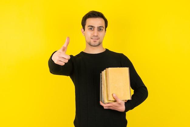Retrato de jovem segurando livros universitários na parede amarela