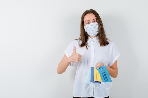 Retrato de jovem segurando máscaras médicas