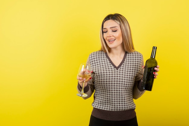 Retrato de jovem segurando o copo e a garrafa de vinho branco.