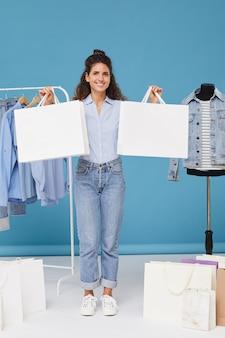 Retrato de jovem segurando sacolas de compras e sorrindo com roupas no cabide ao fundo