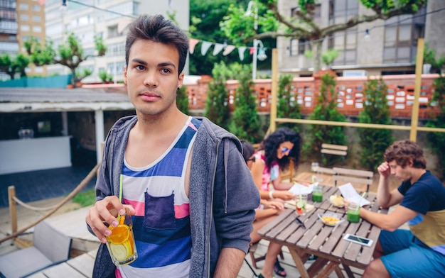 Retrato de jovem segurando um coquetel de água com infusão ao ar livre com os amigos sentados ao redor da mesa em um dia de verão