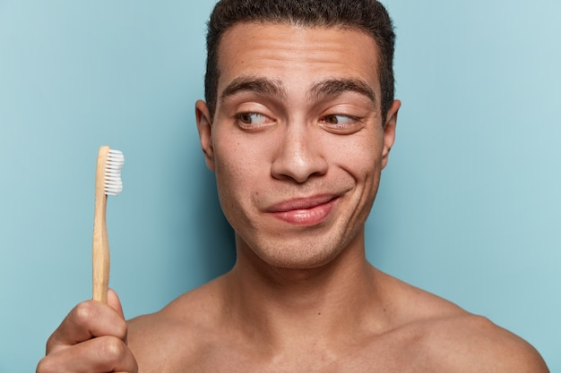 Retrato de jovem segurando uma escova de dentes