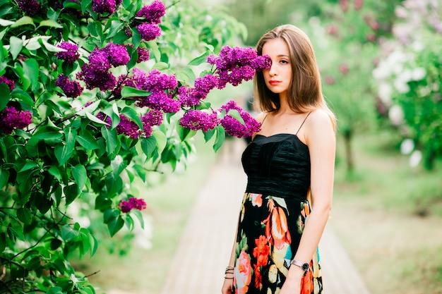 Retrato de jovem sensual com cabelos longos, desfrutando de anf relaxante no parque florescendo primavera.