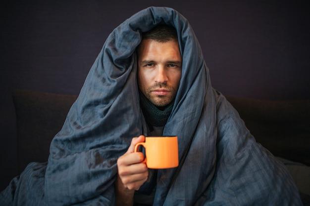 Retrato de jovem senta-se na cama e coberto com um cobertor azul escuro. ele segura uma xícara de chá laranja. cara parece na câmera. ele é sério. jovem é sem emoção.
