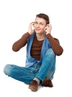 Retrato de jovem sentado no chão com fones de ouvido, isolado no fundo branco