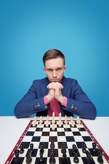 Retrato de jovem sério e focado, sentado à mesa e olhando para o concorrente enquanto joga xadrez