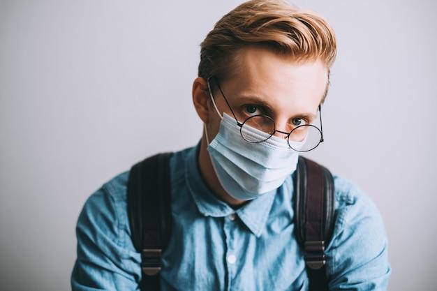 Retrato de jovem sério, estudante universitário com mochila, usa óculos transparentes e máscara médica descartável