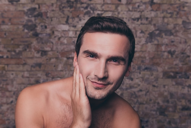 Retrato de jovem sério nu após o banho tocando seu rosto