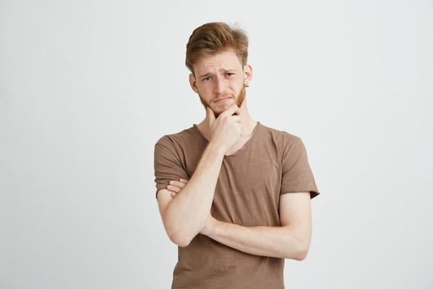 Retrato de jovem sério pensando considerando.
