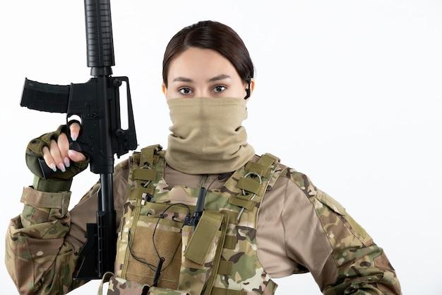 Retrato de jovem soldado camuflado com metralhadora parede branca