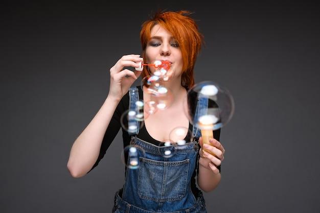 Retrato de jovem soprando bolhas sobre fundo cinza.