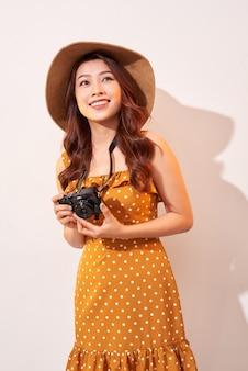 Retrato de jovem sorridente alegre tirando foto com inspiração e vestido de verão. menina segurando a câmera retro. modelo posando na parede bege com chapéu
