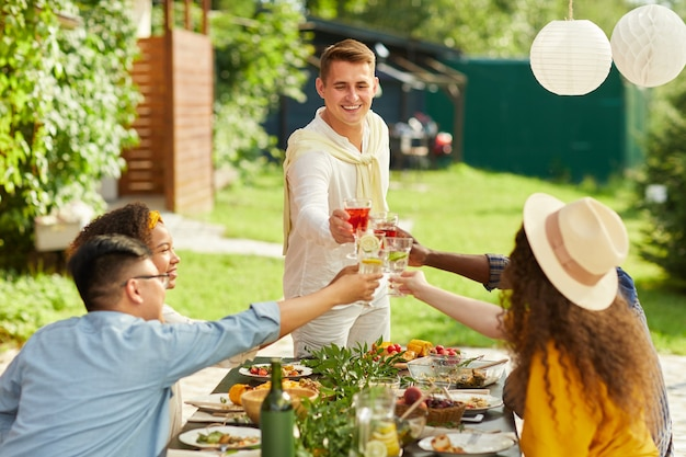 Retrato de jovem sorridente brindando com amigos enquanto desfruta de um jantar no terraço ao ar livre no verão