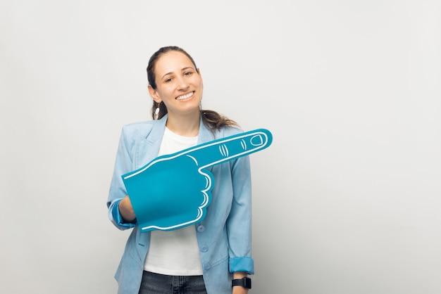Retrato de jovem sorridente casual apontando para longe com a luva de leque azul