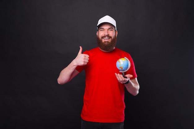 Retrato de jovem sorridente com barba aparecendo o polegar e segurando o globo sobre fundo preto