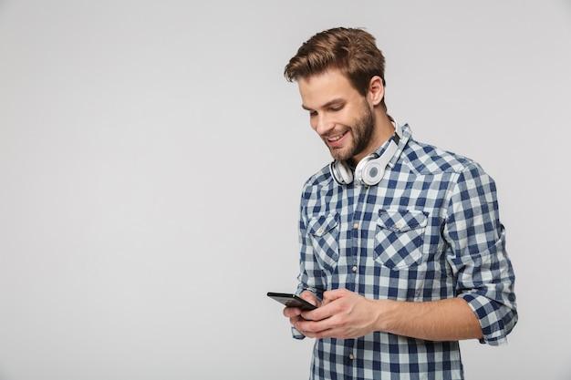 Retrato de jovem sorridente com fones de ouvido usando celular isolado na parede branca