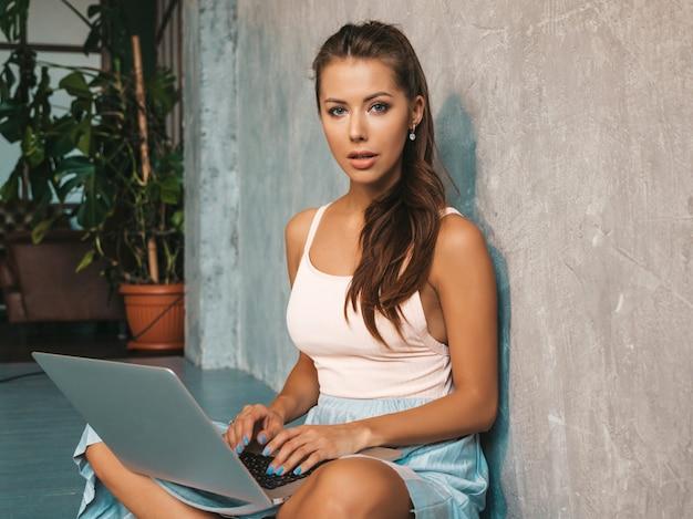 Retrato de jovem sorridente e criativo. linda garota sentada no chão perto da parede cinza no interior. modelo usando o notebook. mulher vestida com roupas hipster