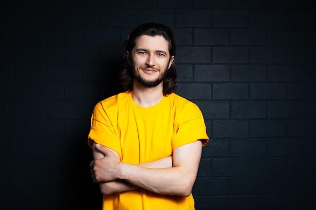 Retrato de jovem sorridente em camisa amarela em fundo de parede de tijolo preto.