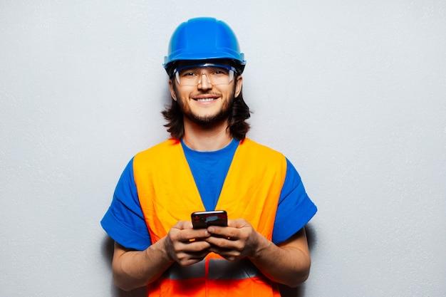 Retrato de jovem sorridente engenheiro trabalhador da construção civil usando smartphone. vestindo equipamento de segurança; capacete azul, óculos transparentes e colete laranja.