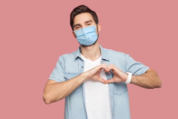 Retrato de jovem sorridente feliz com máscara médica cirúrgica na camisa azul em pé com amor gesto com a mão no coração e olhando para a câmera sorrindo. tiro de estúdio interno, isolado no fundo rosa.
