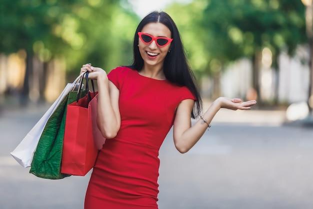 Retrato de jovem sorridente feliz com sacos de compras, desfrutando de compras