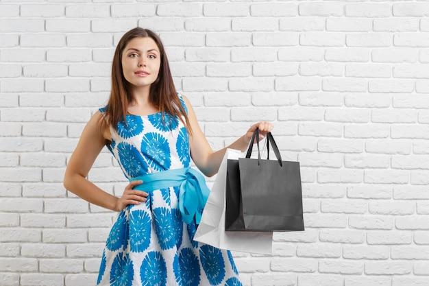 Retrato de jovem sorridente feliz com sacos de compras