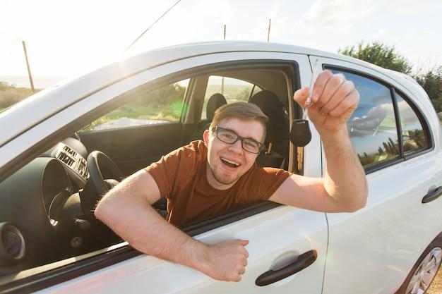 Retrato de jovem sorridente feliz, comprador sentado em seu carro novo e mostrando as chaves do lado de fora do escritório do revendedor.