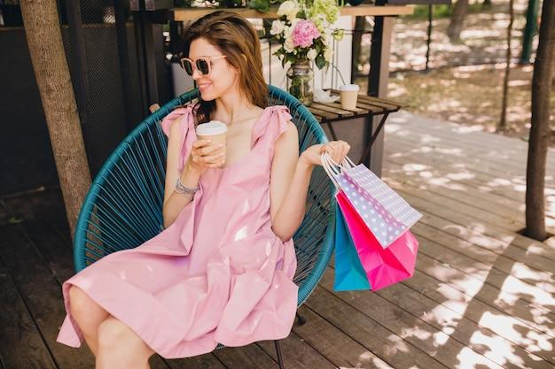 Retrato de jovem sorridente feliz e atraente sentado em um café com sacolas de compras, bebendo café