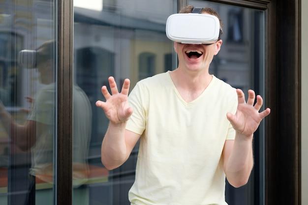 Retrato de jovem sorridente homem atraente usando óculos virtuais