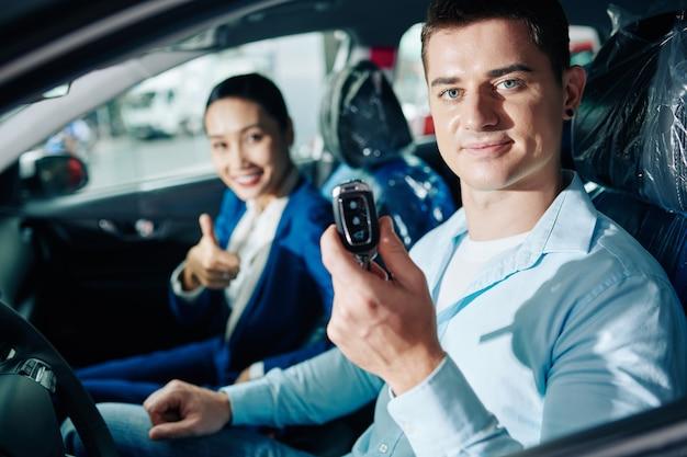 Retrato de jovem sorridente, mostrando as chaves eletrônicas de um carro novo que ele comprou na concessionária