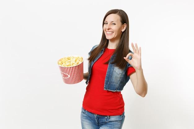 Retrato de jovem sorridente mulher morena atraente em roupas casuais, assistindo a um filme de filme, segurando um balde de pipoca e mostrando sinal de ok, isolado no fundo branco. emoções no conceito de cinema.