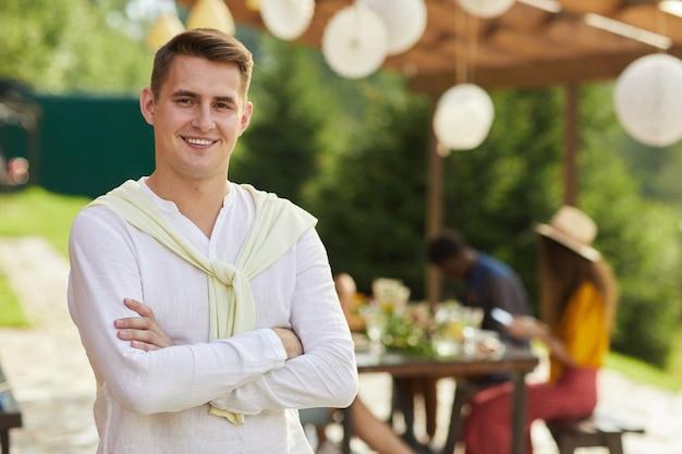 Retrato de jovem sorridente posando ao ar livre no verão com amigos e familiares, jantando no terraço