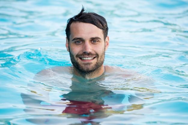Retrato de jovem sorridente relaxando na piscina