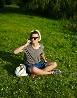 Retrato de jovem sorridente rindo atraente homem elegante moderno em pano casual no chapéu em copos sentado no parque na grama verde, falando no telefone