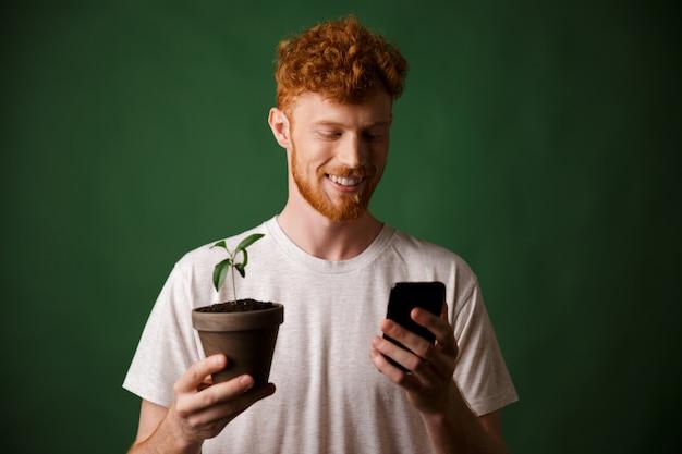 Retrato de jovem sorridente ruiva bonito barbudo jovem, segurando a planta manchada, olhando para o telefone móvel