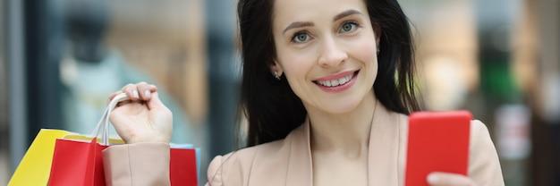 Retrato de jovem sorridente segurando smartphone e pacotes com compras