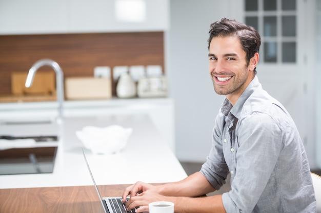 Retrato de jovem sorridente trabalhando no laptop